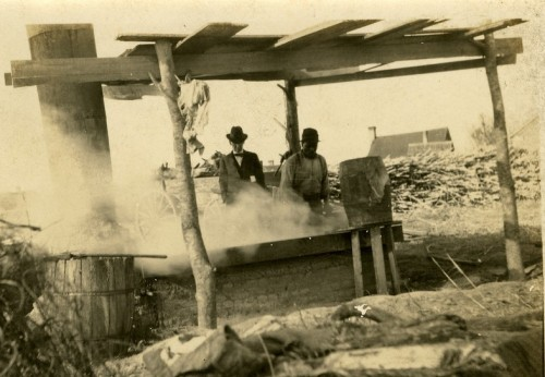 Sugarcane mill. View shows African American male stirring large vat, cooking molasses. Caucasian man observes.